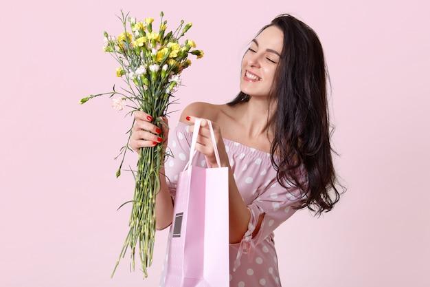 快適な探している若い女性の室内撮影は優しく微笑し、ファッショナブルなドレスを着て、ギフトバッグと花を持っています、明るいピンクでポーズをとって、喜んでいます。女性の日のコンセプト 無料写真