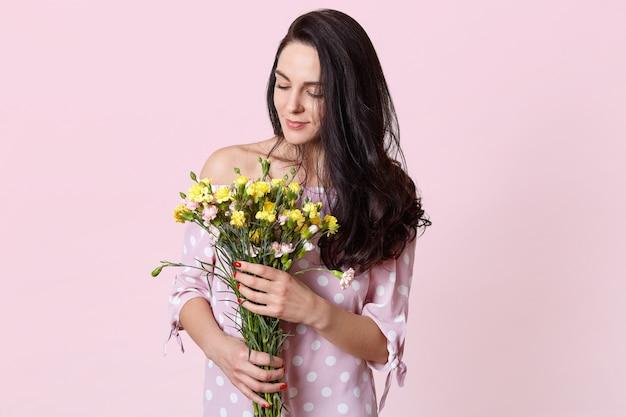 Внутренний снимок довольной темноволосой женской модели держит букет цветов, одетых в модное платье, изолированных на розовом. романтичная привлекательная женщина получает цветы 8 марта Бесплатные Фотографии