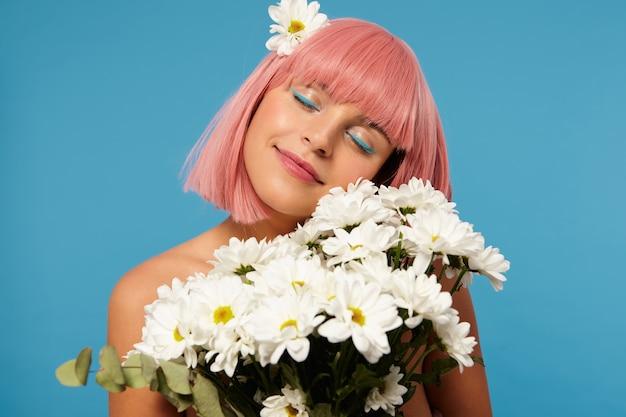 서있는 동안 눈을 감고 꽃의 트러스를 잡고 몹시 웃고있는 밥 이발과 함께 기쁘게 생각하는 젊은 사랑스러운 분홍색 머리 아가씨의 실내 촬영 무료 사진