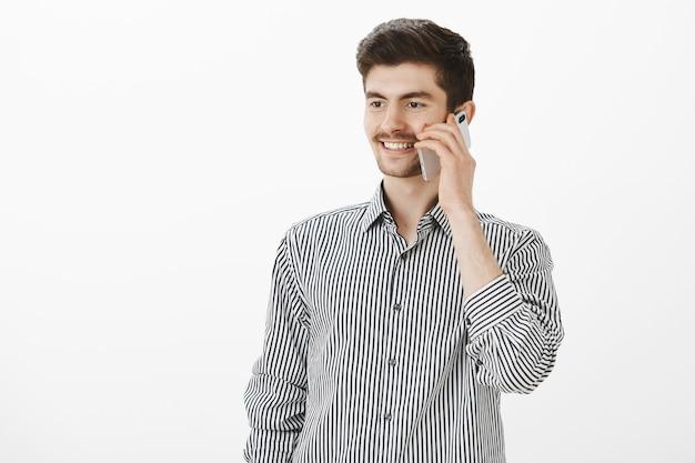 ストライプのシャツを着たポジティブで見栄えの良い自信のある男の屋内ショット、スマートフォンで話している、よそ見と笑顔 無料写真