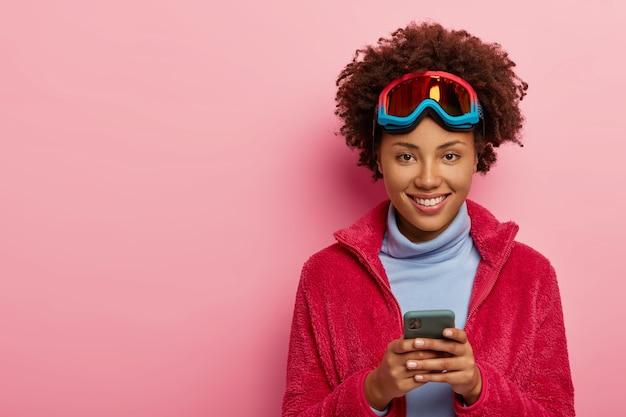 예쁜 스키어 여자의 실내 촬영은 스마트 폰 장치를 사용하고, 스키 마스크를 쓰고, 카메라에 행복하게 미소 짓고, 분홍색 스튜디오 벽 위에 절연되어 있습니다. 무료 사진