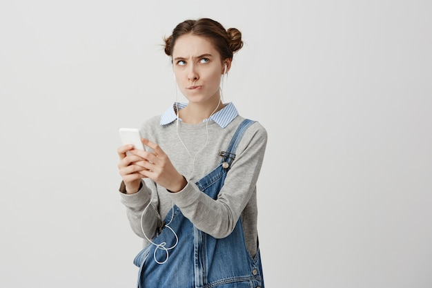 Крытый выстрел обиженный взрослая девушка позирует с ее мобильного телефона в руках, кусая губы в раздражении. лица женского пола оскорбляются с полученным текстом в социальных сетях. человеческие реакции Бесплатные Фотографии