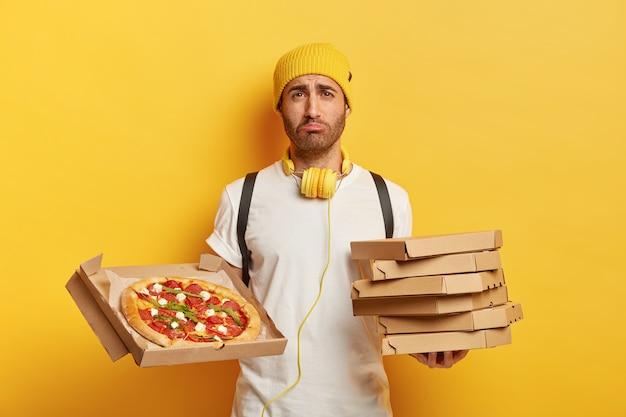 ピザの箱と悲しい配達員の屋内ショット 無料写真