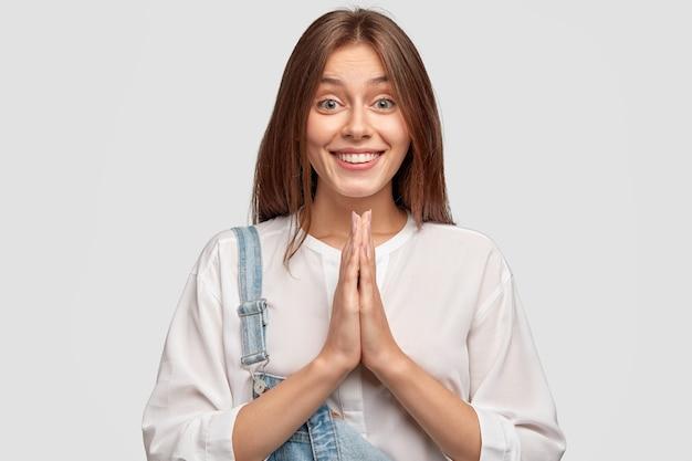 Снимок довольной красивой женщины в помещении, умоляющей о пощаде, с позитивным выражением лица, нежной улыбкой, держащей ладони в молитвенном жесте Бесплатные Фотографии