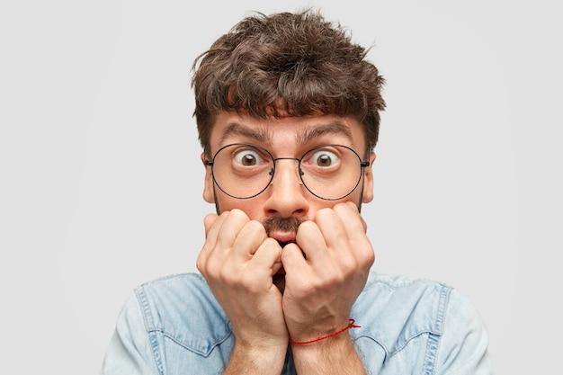怖がっている神経質な男の学生の屋内ショットは、指の爪を噛み、恐怖で見つめ、黒髪をしています 無料写真