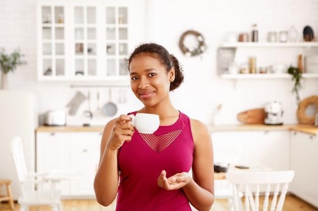公園で走る前に朝のルーチンを持ち、白いマグカップを持って、淹れたてのコーヒーを楽しんでいるスタイリッシュなトップの自信を持って美しい楽しい若い黒人の暗い肌の女性の屋内ショット 無料写真