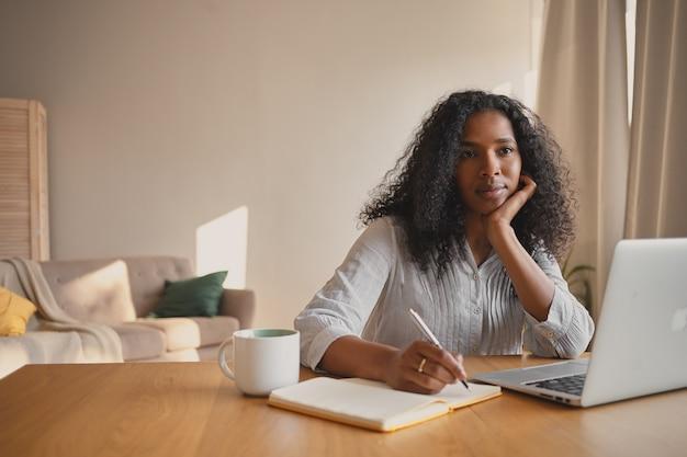 ラップトップを使用してリモートで作業し、マグカップと日記を持ってホームオフィスに座って、書き留めて、一日の計画を立てるウェーブのかかった髪の深刻な美しい若い混血自営業の女性の屋内ショット 無料写真
