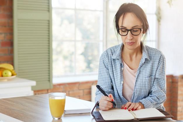 Снимок в помещении: серьезная европейская женщина держит ручку, записывает информацию, которую нашла в интернете или записывает в блокноте, сидит за деревянным кухонным столом с соком. Бесплатные Фотографии