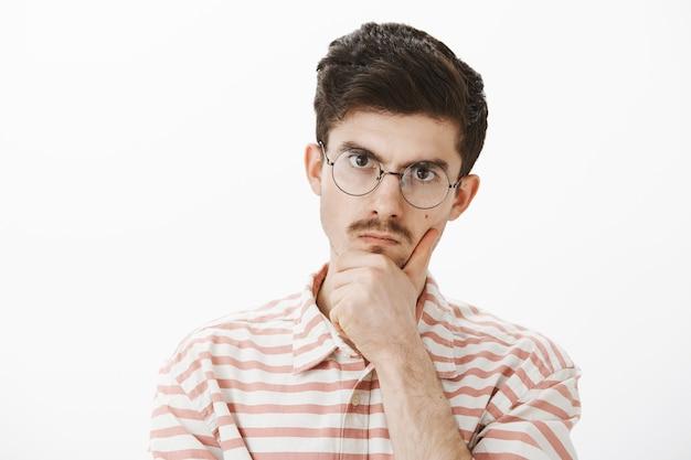 Снимок в помещении: серьезный, сосредоточенный, сердитый старший брат с усами в модных очках, держащий руку за подбородок и смотрящий с недовольным раздраженным выражением лица, решающий сложную проблему через серую стену Бесплатные Фотографии