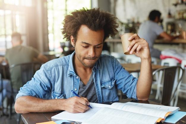 深刻なハンサムな黒人男性の学生が家の割り当てに取り組んでいる間、コーヒーを飲みながら、ペンを使用してコピーブックに書き留め、焦点を絞った表情でノートを見て、唇を追いかけている様子の室内撮影 無料写真