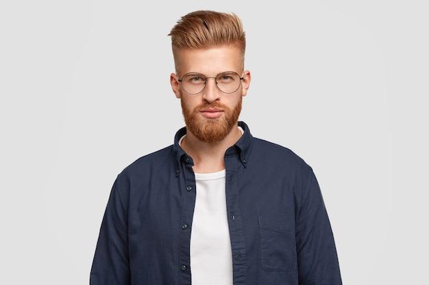 В помещении: серьезный рыжий юноша с густой рыжей бородой, усами, уверенно выглядит, носит модную рубашку, имеет специфическую внешность. Бесплатные Фотографии