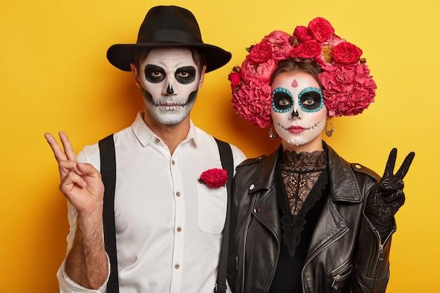 特別な怖い衣装を着た真面目な女性と男性の屋内ショット、平和の勝利のジェスチャーをし、恐ろしい顔をするための鮮やかな化粧をし、メキシコの伝統的な休日を祝います 無料写真