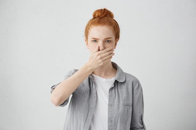 欲求不満を感じて秘密または機密情報を保持する兆候として手で口を覆っているカジュアルな服を着ている生姜髪の深刻な若い白人女性の屋内撮影 無料写真
