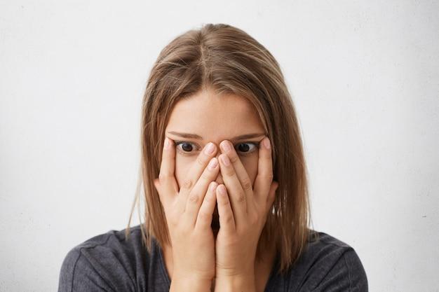 Снимок шокированной, напуганной или разочарованной молодой женщины, закрывающей лицо руками, с глазами, полными ужаса и паники. Бесплатные Фотографии