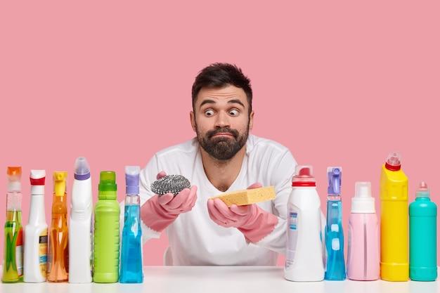 驚いたあごひげを生やした男の屋内ショットは、目を飛び出させて見え、カジュアルな服を着て、さまざまな洗剤を使用しています 無料写真