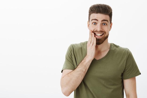 手のひらで眉毛を上げ、白い壁の上の幸せから笑っているスリル満点で陽気な顔に頬をむくっている頬にキスされている驚いて幸せで興奮している見栄えの良い男の屋内ショット 無料写真