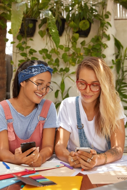 現代のテクノロジーに夢中になっている2人の女子学生の屋内ショット 無料写真
