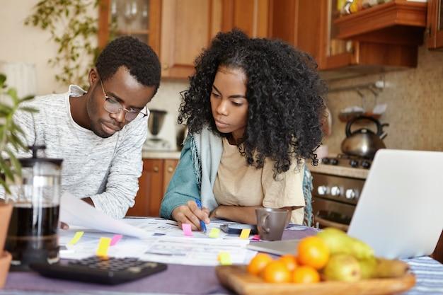 彼らの財政を分析する若いアフリカの家族の屋内撮影 無料写真