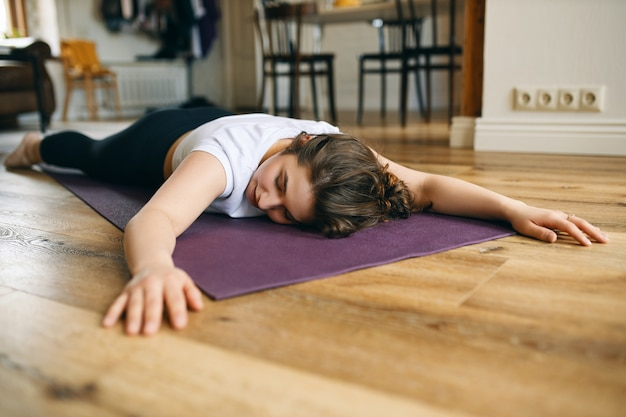 Снимок в помещении молодой кавказской женщины в спортивной одежде, лежащей на животе на коврике с вытянутыми вперед руками, отдыхающей в успокаивающей позе между асанами, занимающейся хатха-йогой дома, расслабляющей тело Бесплатные Фотографии