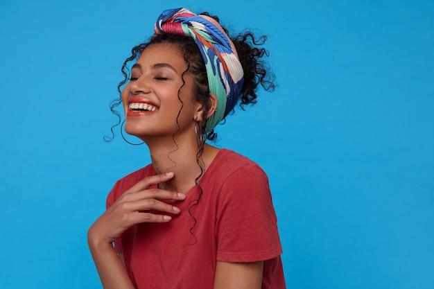 Снимок молодой веселой темноволосой женщины в помещении, держащей поднятой рукой на груди и радостно смеющейся с закрытыми глазами, изолированной на синей стене Бесплатные Фотографии