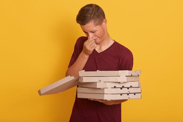 Внутренняя съемка молодого красивого работника доставляющего покупки на дом с плохим запахом испортила pixxa, мужчина держа коробки коробки, представляя изолированный на желтом цвете, парень нося вскользь одежду. концепция доставки. Бесплатные Фотографии
