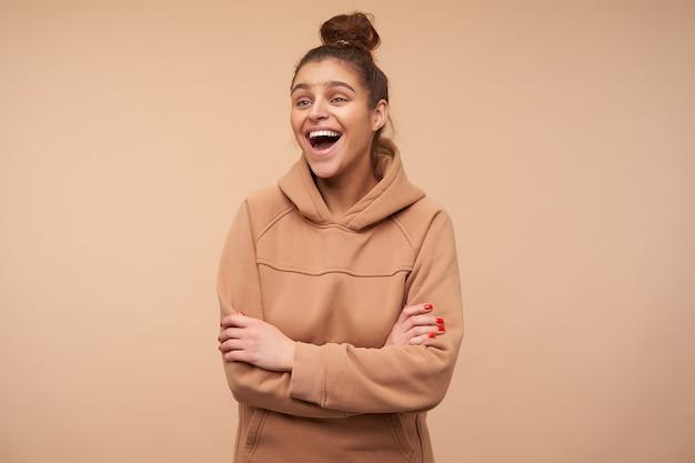 빨간 매니큐어가 높은 정신에 있고 팔을 교차 베이지 색 벽 위에 서있는 동안 행복하게 웃고있는 젊은 사랑스러운 갈색 머리 아가씨의 실내 촬영 무료 사진