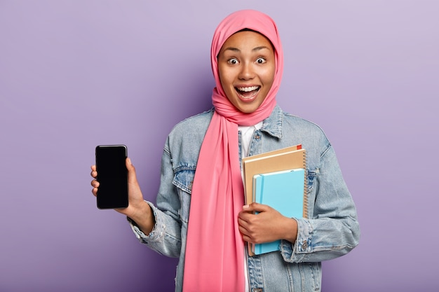 Indoor shot of optimistic dark skinned muslim woman introduces cool gadget Free Photo