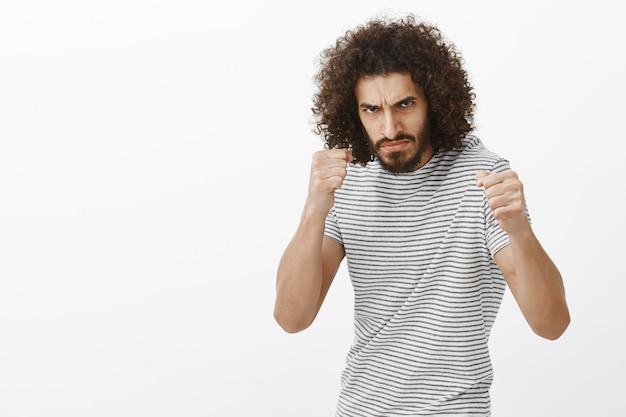 Tiro al coperto di bullo indignato con barba e taglio di capelli afro, in piedi nella posa di boxe con i pugni chiusi, aggrottando la fronte al nemico, essendo pronto a combattere Foto Gratuite