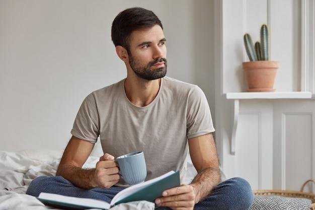 Tiro al coperto di pensieroso giovane ragazzo caucasico con folta barba, essendo immerso nei pensieri, tiene il libro e la tazza di tè, pone sul letto Foto Gratuite