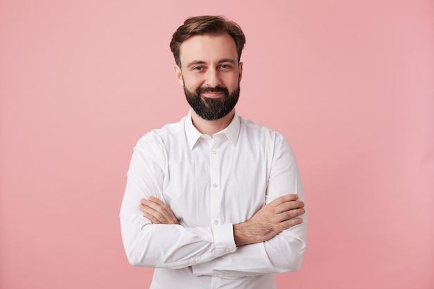 Tiro al coperto di piacevole giovane barbuto uomo bruna con acconciatura alla moda attraversando la mano sul petto mentre si trovava sul muro rosa, vestito con una camicia bianca Foto Gratuite
