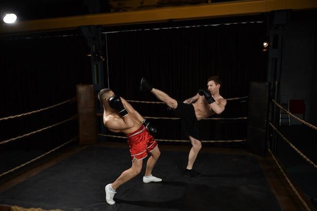 Tiro al coperto di combattenti misti professionisti giovani europei maschi con torso nudo boxe sul ring: maschio in pantaloncini neri allungando la gamba, andando a calciare il suo nemico in pantaloni rossi proprio in faccia Foto Gratuite