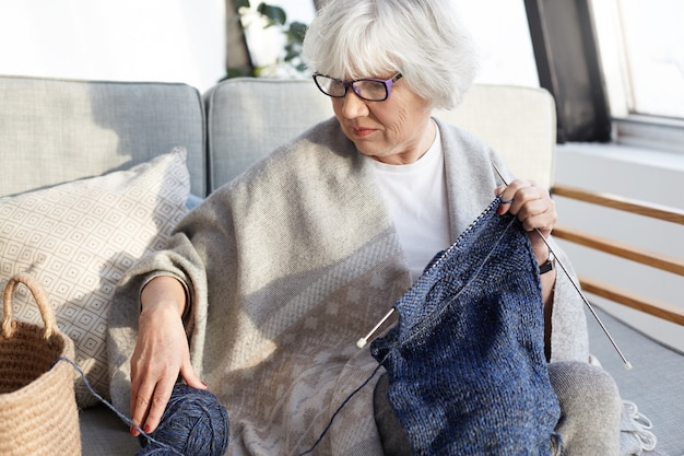 Indoor shot of serious concentrated elderly woman with gray hair sitting on couch in living room wearing glasses, knitting warm winter clothes for her internet website, selling homemade goods online Free Photo
