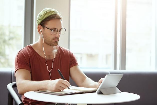 Tiro al coperto di serio studente universitario in occhiali e cappello, scrive note dal tablet Foto Gratuite