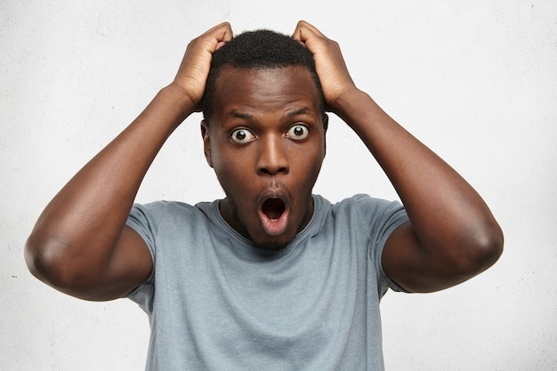 Indoor shot of stunned bug-eyed young african american student or customer looking with surprised expression, keeping hands on his head, shocked with big sale prices while shopping Free Photo