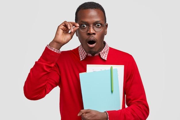Tiro al coperto di un ragazzo dalla pelle scura stupefatto mantiene la mascella aperta, indossa abiti e occhiali rossi, trasporta libri di testo, scrive un rapporto scientifico Foto Gratuite