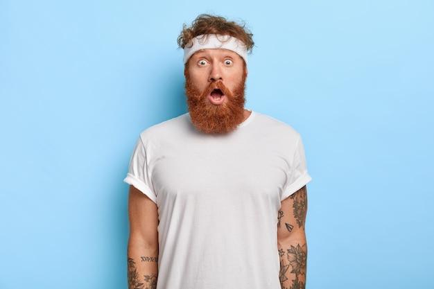 Tiro al coperto di uomo barbuto sorpreso con i capelli rossi, guarda con stupore, fa ginnastica ogni giorno Foto Gratuite