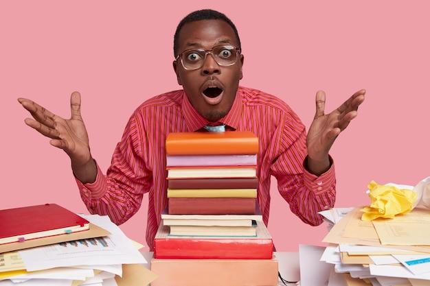 Tiro al coperto di sorpreso maschio nero allarga le mani, ha un'espressione stupita, mantiene la mascella aperta, si siede alla scrivania con una pila di libri di testo Foto Gratuite