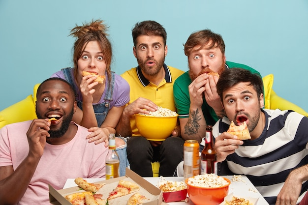 Indoor shot of surprised mixed race friends, eat popcorn, pizza, have fearful panicked faces, enjoy watching horror films, have free time on evening weekend, sit on sofa. people and free time concept Free Photo