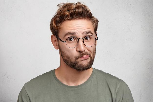 Tiro al coperto di un giovane sospettoso che curva le labbra, indossa gli occhiali, ha esitazioni Foto Gratuite