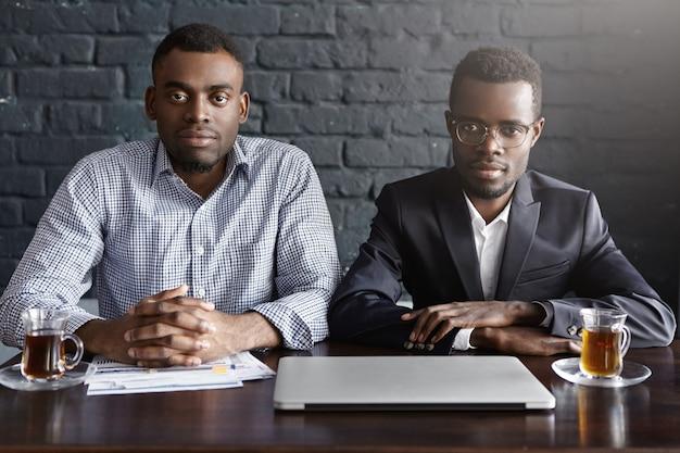 Tiro al coperto di due uomini d'affari di successo che hanno riunione nell'interiore dell'ufficio moderno Foto Gratuite