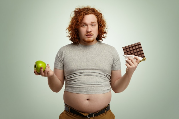 Indoor shot of uncertain confused plump young male facing hard choice as he has to chose between fresh organic apple in one hand and delicious bar of chocolate in other. dilemma, diet and food Free Photo