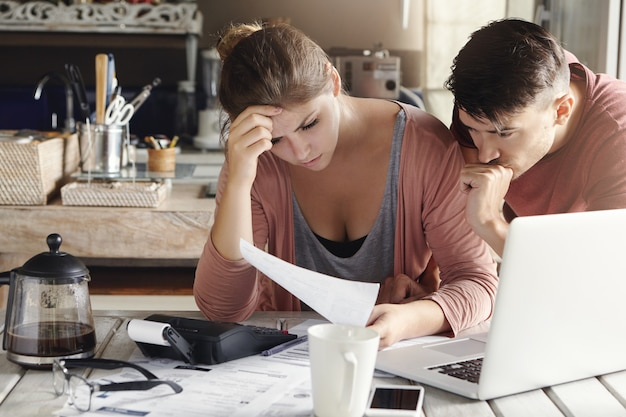 Indoor shot of unhappy young family distressed with financial problems and mounting bills, reading document with frustrated looks while calculating domestic finances together in their kitchen Free Photo