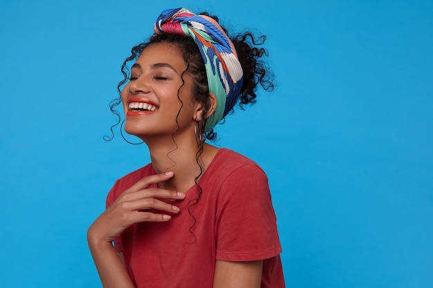 Indoor shot of young cheerful dark haired woman keeping raised hand on her chest and laughing happily with closed eyes, isolated over blue wall Free Photo