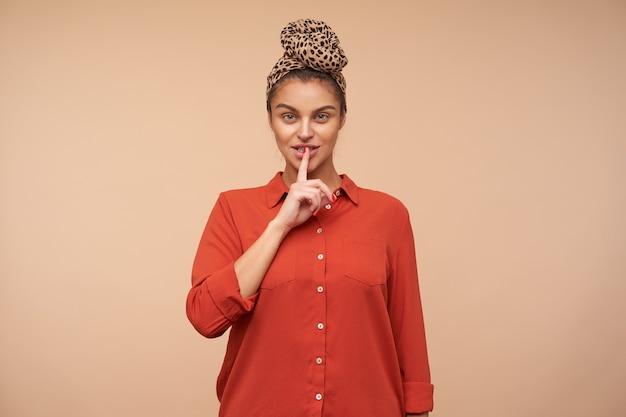 Tiro al coperto di giovane donna graziosa del brunette che alza la mano nel gesto di silenzio mentre chiede di mantenere il silenzio, isolato sopra il muro beige in fascia e camicia rossa Foto Gratuite
