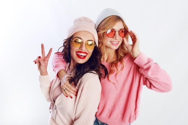 두 여자의 실내 스튜디오 이미지, 세련 된 분홍색 옷과 모자 맞춤법에 행복 친구 함께 재미. 흰 바탕. 트렌디 한 모자와 안경. 무료 사진