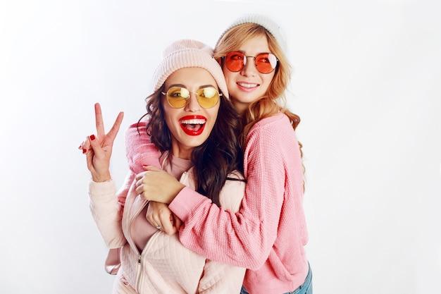 Immagine dello studio dell'interno di due ragazze, amici felici in vestiti rosa alla moda e ortografia del cappello divertente insieme. sfondo bianco Foto Gratuite