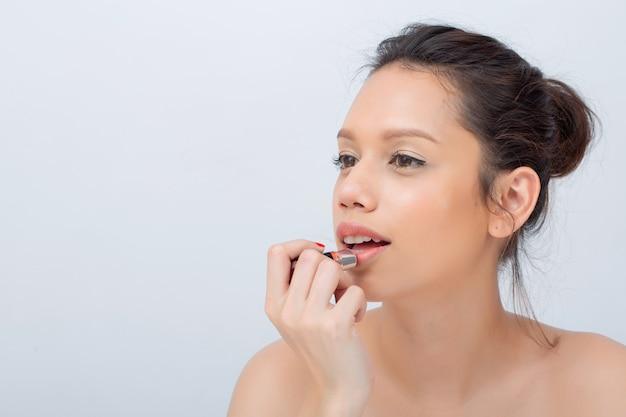 自然化粧品で口紅を広く適用する笑顔の美しいアジア女性の屋内スタジオ撮影 Premium写真