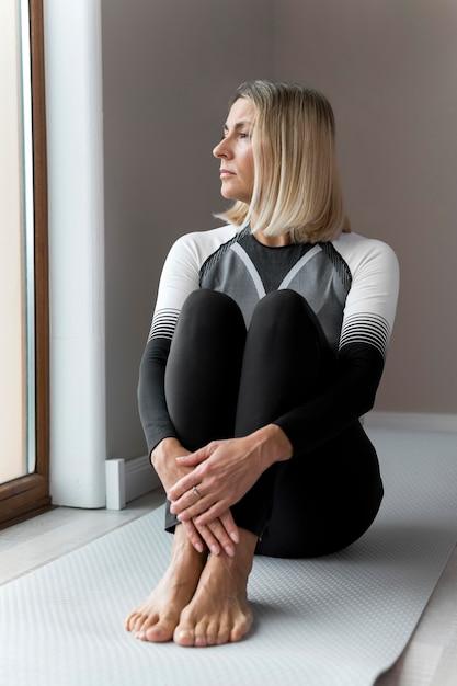 All'interno donna matura seduta e guardando fuori dalla finestra Foto Gratuite