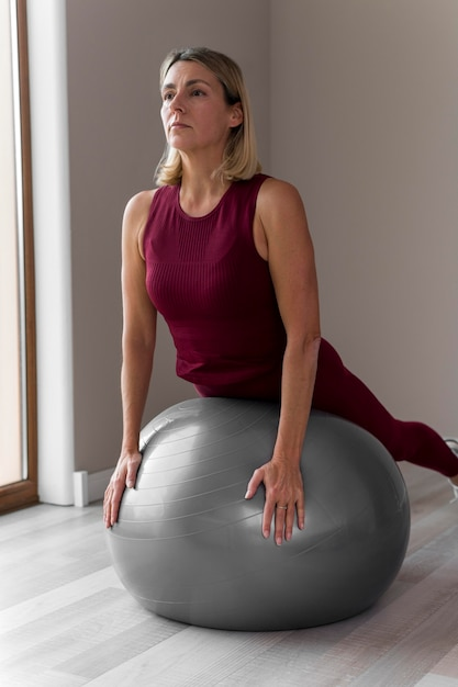 В помещении зрелая женщина с серебряным мячом для фитнеса Бесплатные Фотографии