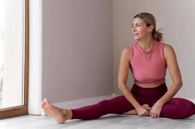 Indoors mature woman wearing pink sport clothes Free Photo